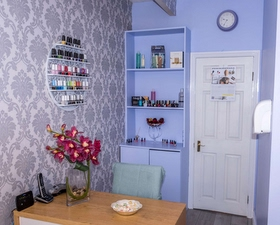 a room in number 10 massage and beauty with a desk and nail polish on the walls